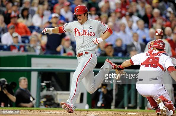 Cole Hamels of the Philadelphia Phillies scores in the third inning ahead of the tag of Wilson Ramos of the Washington Nationals at Nationals Park on...