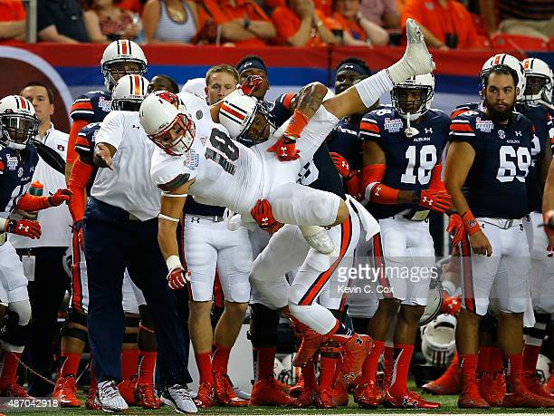 Cole Hikutini of the Louisville Cardinals fails to pull in a reception as he is tackled by Tray Matthews of the Auburn Tigers at Georgia Dome on...