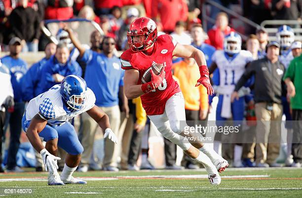 Cole Hikutini of the Louisville Cardinals runs with the ball during the game against the Kentucky Wildcats at Papa John's Cardinal Stadium on...