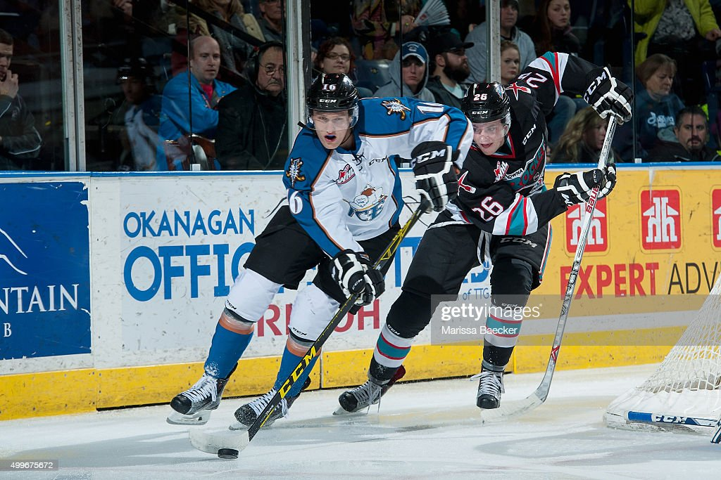 Cole Linaker #26 of Kelowna Rockets back checks Shane Allan #16 of Kootenay Ice as he skates behind the net with the puck on December 2, 2015 at Prospera Place in Kelowna, British Columbia, Canada.