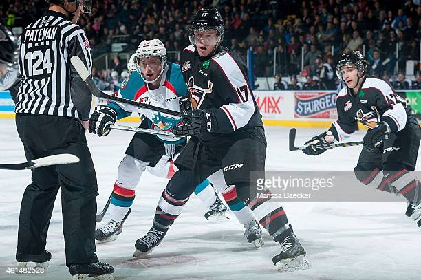 Cole Linaker of Kelowna Rockets checks Tyler Benson of Vancouver Giants on January 7 2015 at Prospera Place in Kelowna British Columbia Canada