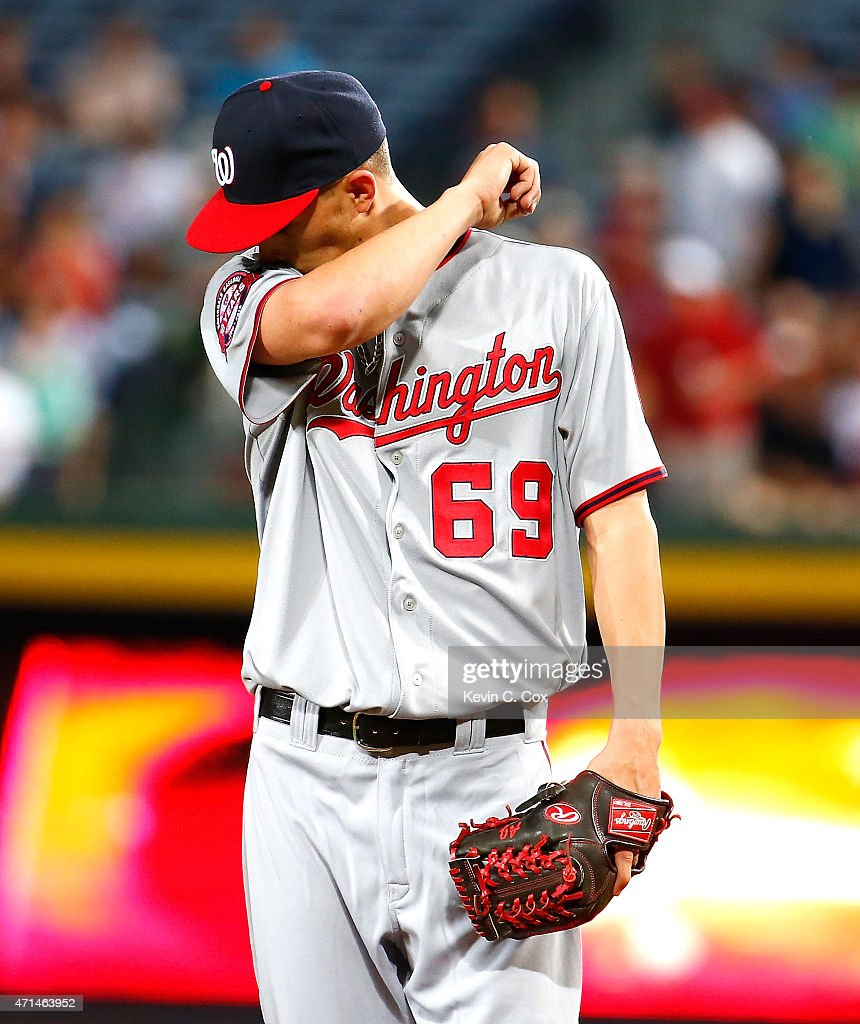 A.J. Cole #69 of the Washington Nationals reacts after giving up a RBI single by Jace Peterson #8 of the Atlanta Braves that scored Kelly Johnson #24 in the second inning at Turner Field on April 28, 2015 in Atlanta, Georgia.