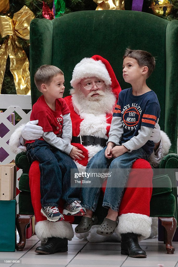 Cole Price, right, contemplates what he wants for Christmas as his brother, Nate, waits for his turn while sitting on Santa's lap, at Dutch Square Center, South Carolina, Thursday, December 20, 2012. Both are from Batesburg-Leesville, South Carolina.
