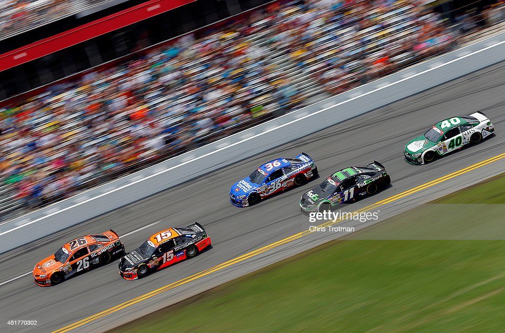 Cole Whitt, driver of the #26 Al's Liner/Scorpion Window Film Toyota, leads Clint Bowyer, driver of the #15 RK Motors Charlotte Toyota, Reed Sorenson, driver of the #36 Golden Corral Chevrolet, Denny Hamlin, driver of the #11 FedEx Ground Toyota, and Landon Cassill, driver of the #40 Newtown Building Supplies Chevrolet, during the NASCAR Sprint Cup Series Coke Zero 400 at Daytona International Speedway on July 6, 2014 in Daytona Beach, Florida.