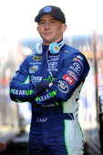 Cole Whitt driver of the Gear Speed Stick Toyota poses between two haulers during practice for the NASCAR Sprint Cup Series Food City 500 at Bristol...