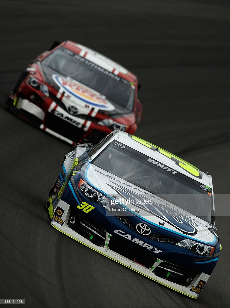 Cole Whitt, driver of the #30 Swan Energy Toyota, leads David Reutimann, driver of the #83 Burger King / Dr Pepper Toyota, during the NASCAR Sprint Cup Series 13th Annual Hollywood Casino 400 at Kansas Speedway on October 6, 2013 in Kansas City, Kansas.