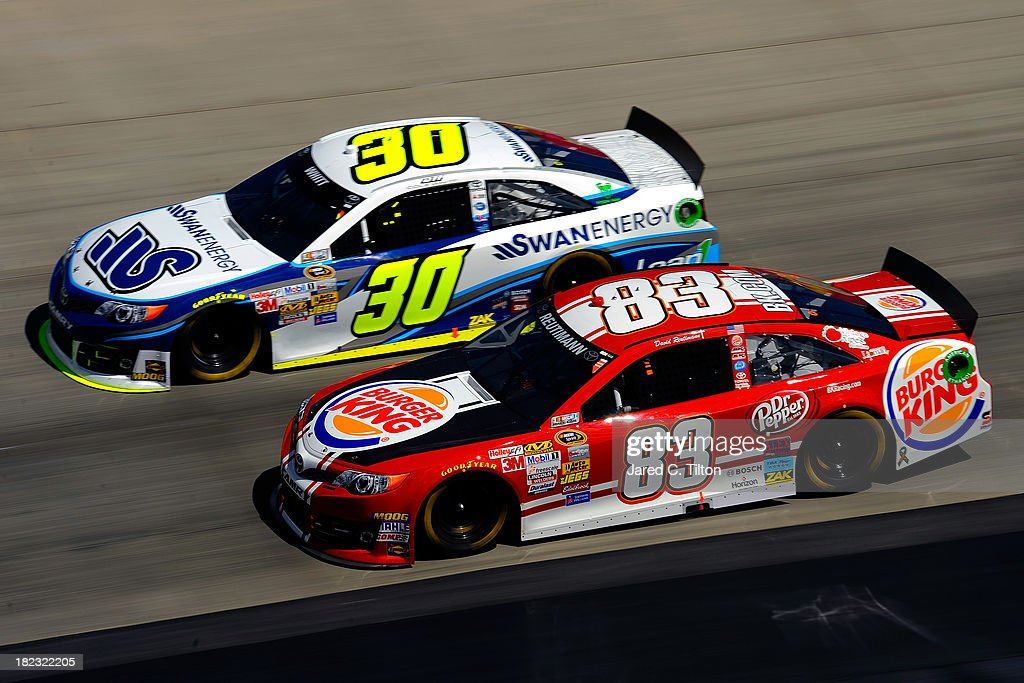 Cole Whitt, driver of the #30 Swan Energy Toyota, races David Reutimann, driver of the #83 Burger King / Dr. Pepper Toyota, during the NASCAR Sprint Cup Series AAA 400 at Dover International Speedway on September 29, 2013 in Dover, Delaware.