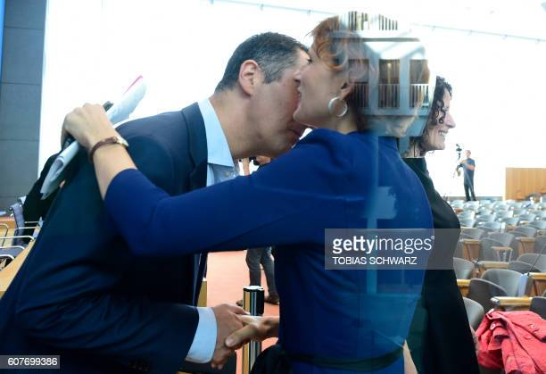 Coleader of the Greens Cem Oezdemir hugs the coleader of the leftwing Die Linke party Katja Kipping prior to a news conference on September 19 2016...