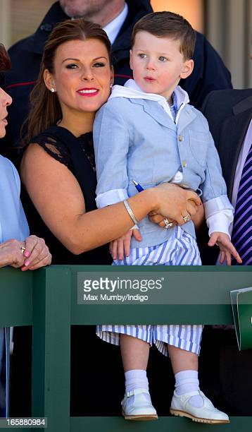 Coleen Rooney and her son Kai Rooney watch the racing as they attend the John Smith's Grand National at Aintree Racecourse on April 6 2013 in...