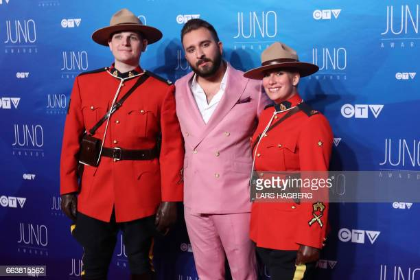 Coleman Hell poses with RCMP officers he arrives on the red carpet before the JUNO awards at the Canadian Tire Centre in Ottawa Ontario on April 2...