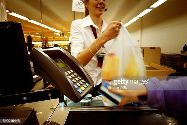 A Coles Myer cashier hands over groceries at the checkout with EFTPOS terminal in the foreground 18 September 2003 THE AGE Picture by JOE ARMAO