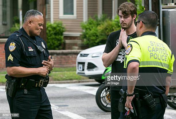 STATES MAY 9 Colin Anhut a native of Raleigh NC is stopped by North Carolina Capitol Police after taping a sign to the gate outside of the Governor's...