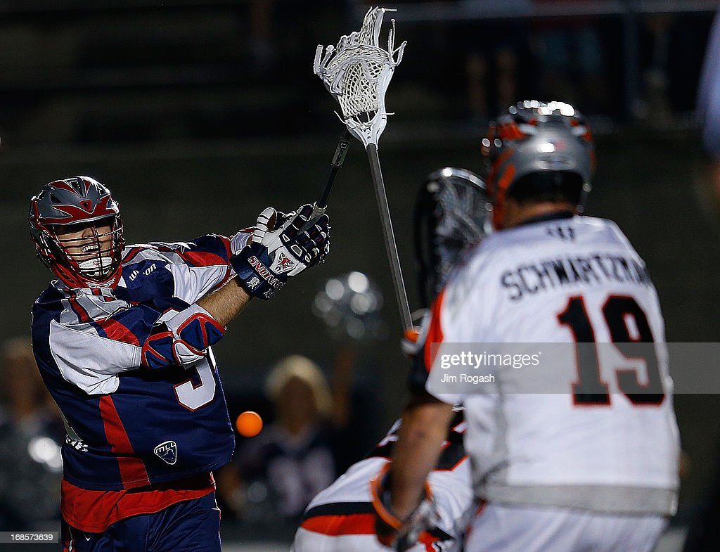 Colin Briggs #34 of the Boston Cannons has his shot stopped by goalie Jesse Schwartzman #19 of the Denver Outlaws in the second half at Harvard Stadium on May 11, 2013 in Boston, Massachusetts.