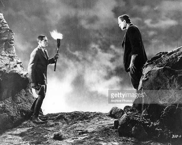 Colin Clive holding torch before the monster Boris Karloff in a scene from the film 'Frankenstein' 1931