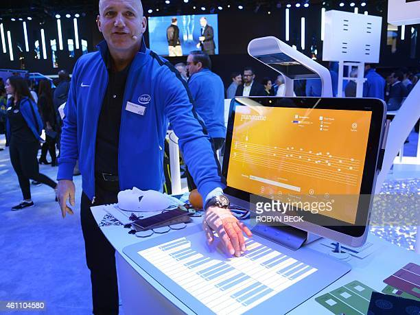 Colin Daymude plays music via a projected piano keyboard as he demonstrates the HP Sprout January 6 2015 at the Intel stand at the Consumer...