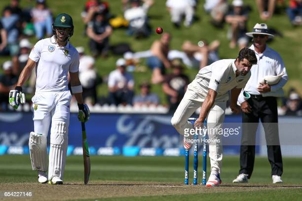 Colin de Grandhomme of New Zealand bowls while Faf du Plessis of South Africa looks on during day two of the test match between New Zealand and South...