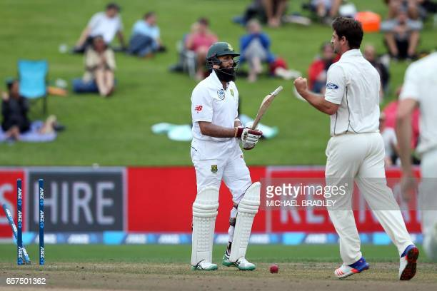 Colin de Grandhomme of New Zealand celebrates the wicket of Hashim Amla of South Africa during day one of the third Test cricket match between New...