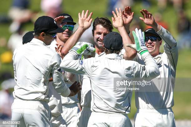 Colin de Grandhomme of New Zealand celebrates with teammates after taking the wicket of Faf du Plessis of South Africa during day two of the test...