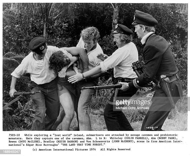 Colin Farrell restrains Bobby Parr with Doug McClure Keith Barron and John McEnery in a scene from the film 'The Land That Time Forgot' 1975