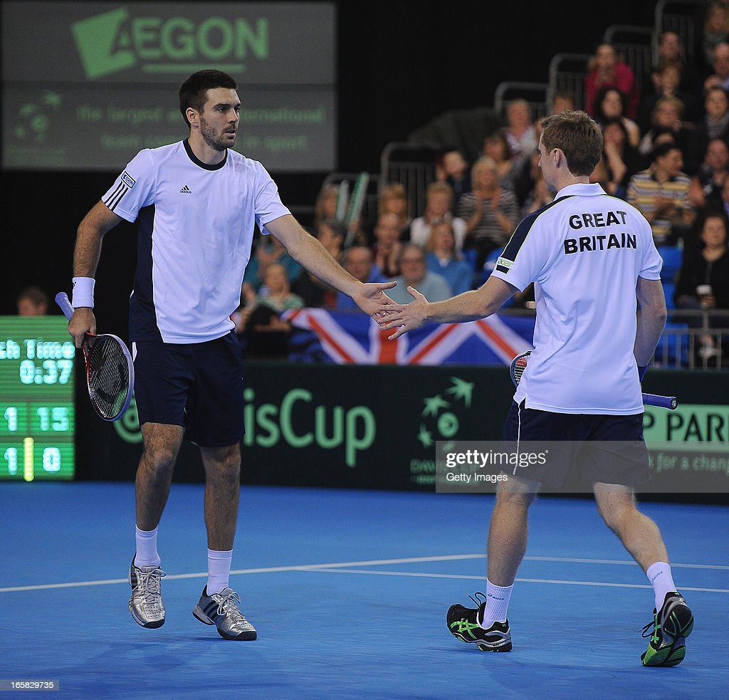 Colin Flemming (L) and Jonny Marray of Great Britain low five after they win a point against Victor Baluda and Igor Kunitsyn of Russia during day two of the Davis Cup match between Great Britain and Russia at Ricoh Arena on April 6, 2013 in Coventry, England.