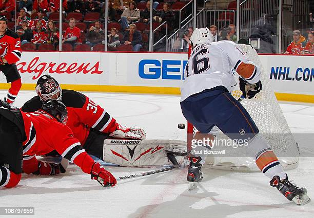 Colin Fraser of the Edmonton Oilers shoots the puck past goalie Martin Brodeur of the New Jersey Devils for the first goal of a hockey game at the...