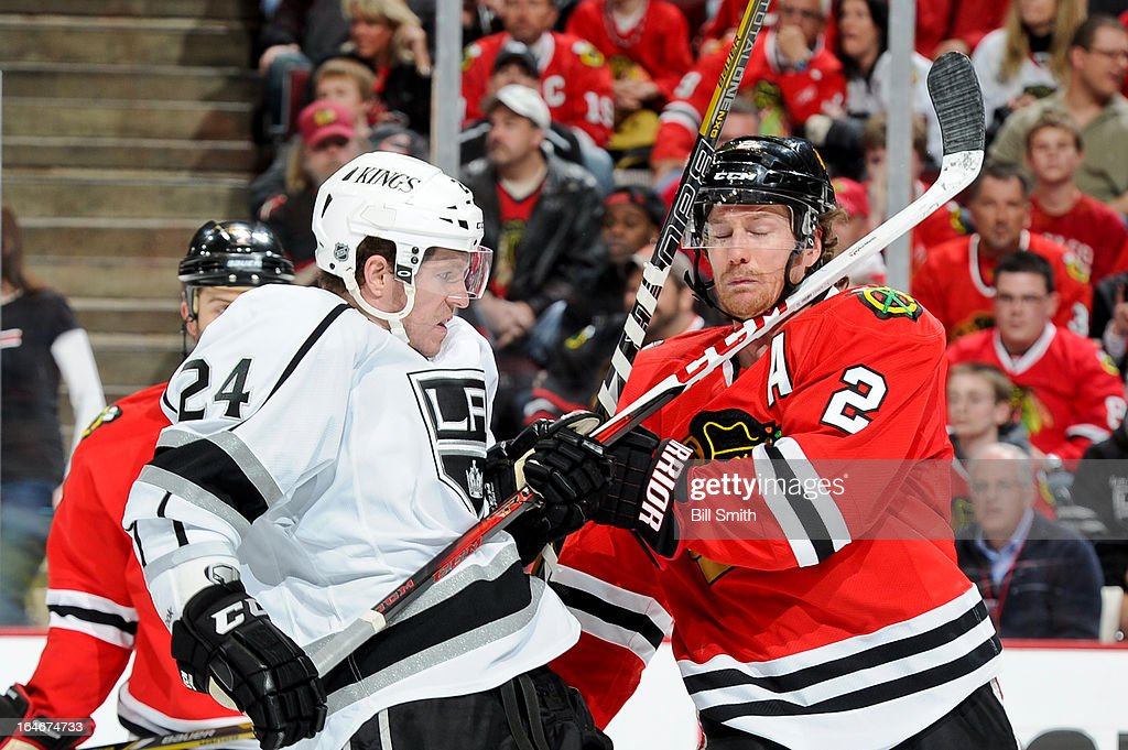 Colin Fraser #24 of the Los Angeles Kings and Duncan Keith #2 of the Chicago Blackhawks get physical during the NHL game on March 25, 2013 at the United Center in Chicago, Illinois.
