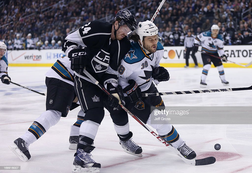 <a gi-track='captionPersonalityLinkClicked' href=/galleries/search?phrase=Colin+Fraser&family=editorial&specificpeople=2225768 ng-click='$event.stopPropagation()'>Colin Fraser</a> #24 of the Los Angeles Kings is checked off the puck by Bracken Kearns #38 of the San Jose Sharks in the second period of Game Two of the Western Conference Semifinals during the 2013 NHL Stanley Cup Playoffs at Staples Center on May 16, 2013 in Los Angeles, California. The Kings defeated the Sharks 4-3.