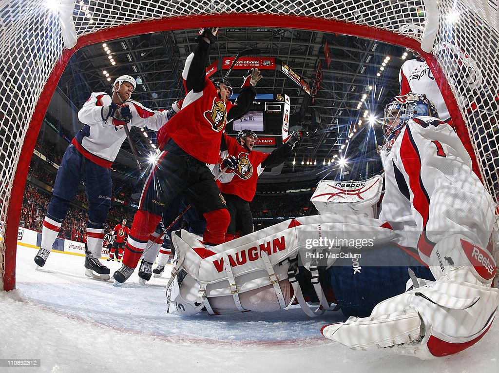 Colin Greening and Bobby Butler of the Ottawa Senators celebrate a goal while Semyon Varlamov of the Washington Capitals sits in his net during a...