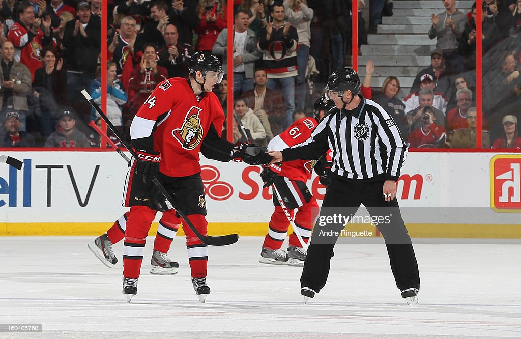 Colin Greening #14 of the Ottawa Senators collects the puck from linesman Andy McElman with which teammate Mika Zibanejad (not pictured) scored his first career NHL goal during the second period of a game against the the Montreal Canadiens on January 30, 2013 at Scotiabank Place in Ottawa, Ontario, Canada.