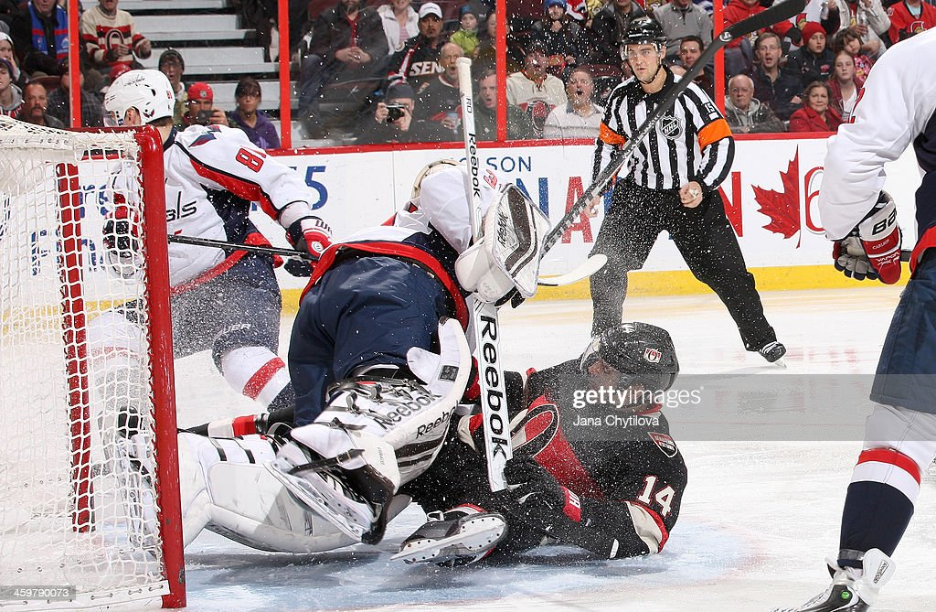 <a gi-track='captionPersonalityLinkClicked' href=/galleries/search?phrase=Colin+Greening&family=editorial&specificpeople=7183741 ng-click='$event.stopPropagation()'>Colin Greening</a> #14 of the Ottawa Senators collides with goalie <a gi-track='captionPersonalityLinkClicked' href=/galleries/search?phrase=Philipp+Grubauer&family=editorial&specificpeople=5649884 ng-click='$event.stopPropagation()'>Philipp Grubauer</a> #31 of the Washington Capitals during an NHL game at Canadian Tire Centre on December 30, 2013 in Ottawa, Ontario, Canada.