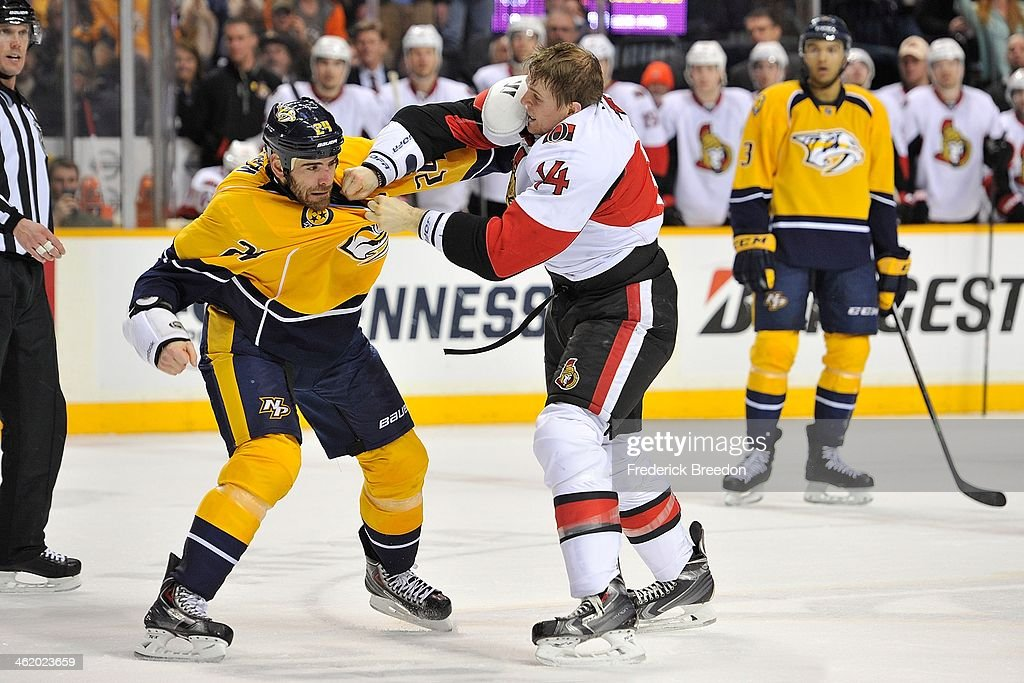 Colin Greening of the Ottawa Senators fights against Eric Nystrom of the Nashville Predators at Bridgestone Arena on January 11 2014 in Nashville...