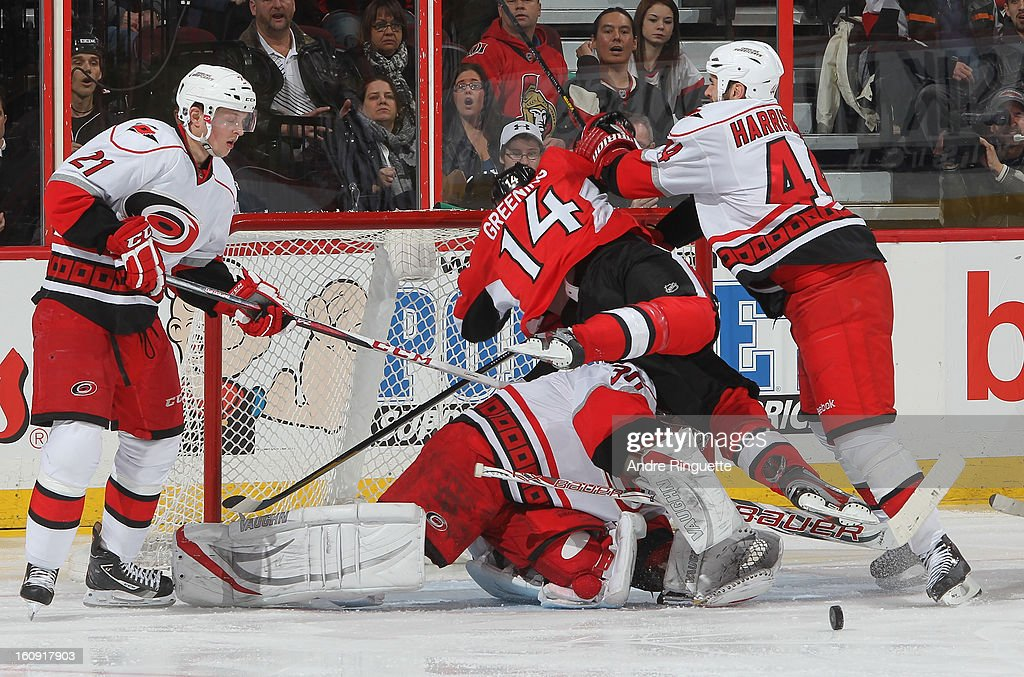 Colin Greening #14 of the Ottawa Senators is knocked over goalie Cam Ward #30 of the Carolina Hurricanes by Jay Harrison #44 as Drayson Bowman #21 looks for the rebound on February 7, 2013 at Scotiabank Place in Ottawa, Ontario, Canada.
