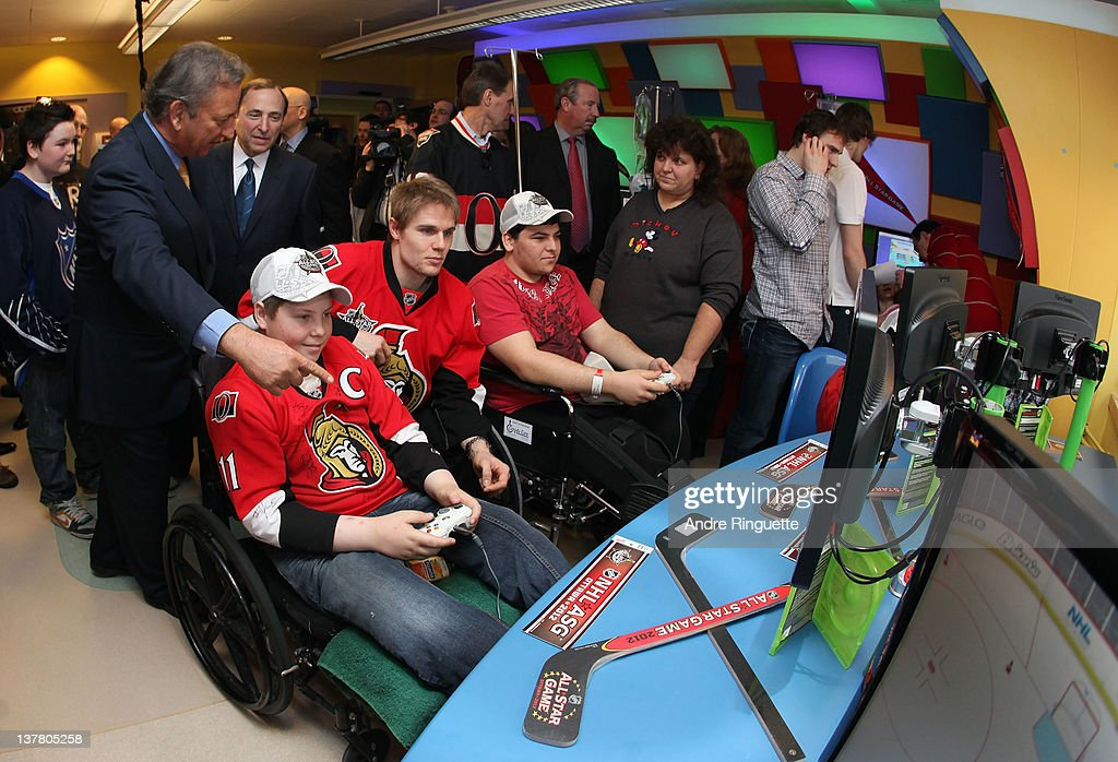 Colin Greening #14 of the Ottawa Senators plays a video game with young patients as NHL Commissioner <a gi-track='captionPersonalityLinkClicked' href=/galleries/search?phrase=Gary+Bettman&family=editorial&specificpeople=215089 ng-click='$event.stopPropagation()'>Gary Bettman</a> (3rd from L) and Ottawa Senators Owner Eugene Melnyk (2nd from L) look on at the unveiling of the NHL All-Star Legacy Playroom at Children's Hospital of Eastern Ontario on January 27, 2012 in Ottawa, Canada.