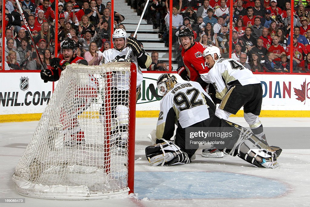 <a gi-track='captionPersonalityLinkClicked' href=/galleries/search?phrase=Colin+Greening&family=editorial&specificpeople=7183741 ng-click='$event.stopPropagation()'>Colin Greening</a> #14 of the Ottawa Senators scores the game-winning goal in double overtime with the help of Andre Benoit #61 as <a gi-track='captionPersonalityLinkClicked' href=/galleries/search?phrase=Tomas+Vokoun&family=editorial&specificpeople=202179 ng-click='$event.stopPropagation()'>Tomas Vokoun</a> #92 of the Pittsburgh, <a gi-track='captionPersonalityLinkClicked' href=/galleries/search?phrase=Matt+Cooke&family=editorial&specificpeople=592551 ng-click='$event.stopPropagation()'>Matt Cooke</a> #24 and Mark Eaton #4 look on in Game Three of the Eastern Conference Semifinals during the 2013 NHL Stanley Cup Playoffs at Scotiabank Place on May 19, 2013 in Ottawa, Ontario, Canada.