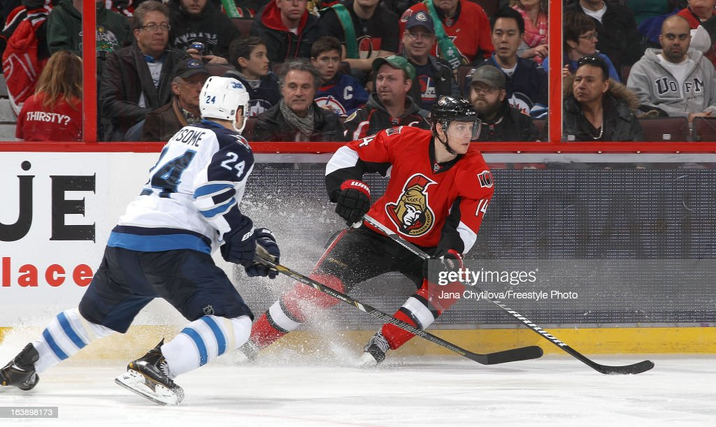 Colin Greening #14 of the Ottawa Senators shoots the puck against Grant Clitsome #24 of the Winnipeg Jets, during an NHL game at Scotiabank Place, on March 17, 2013 in Ottawa, Ontario, Canada.