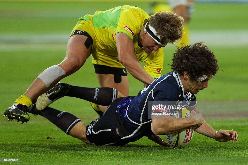 Colin Gregor of Scotland is tackled by Lewis Holland of Australia in the final plate match between Scotland and Australia during the 2013 Wellington Sevens at Westpac Stadium on February 2, 2013 in Wellington, New Zealand.