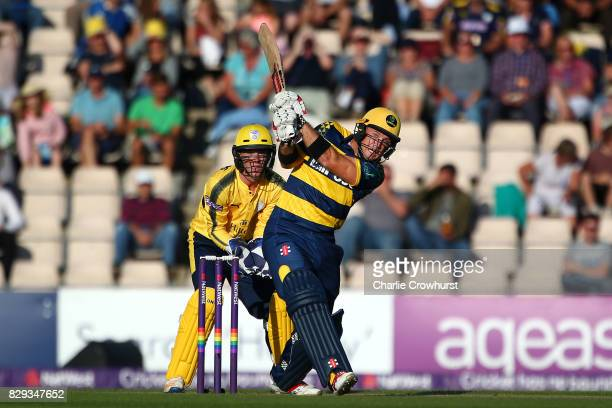 Colin Ingram of Glamorgan hits out while Hampshire wicket keeper Calvin Dickinson looks on during the NatWest T20 Blast match between Hampshire and...