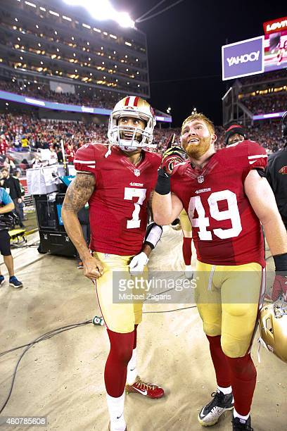 Colin Kaepernick and Bruce Miller of the San Francisco 49ers watch a replay of Kapernick's 90yard touchdown on the big screen during the game against...