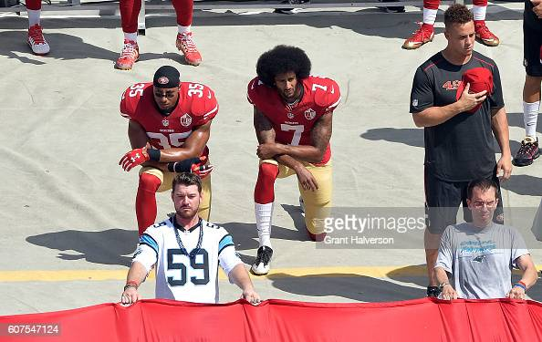 Colin Kaepernick and Eric Reid of the San Francisco 49ers kneel during the national anthem before their game against the Carolina Panthers at Bank of...