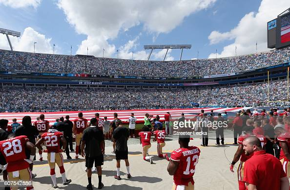 Colin Kaepernick and teammate Eric Reid of the San Francisco 49ers kneel during the national anthem before their game against the Carolina Panthers...