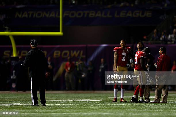 Colin Kaepernick Frank Gore and head coach Jim Harbaugh of the San Francisco 49ers wait on the field during a power outage that occured in the third...