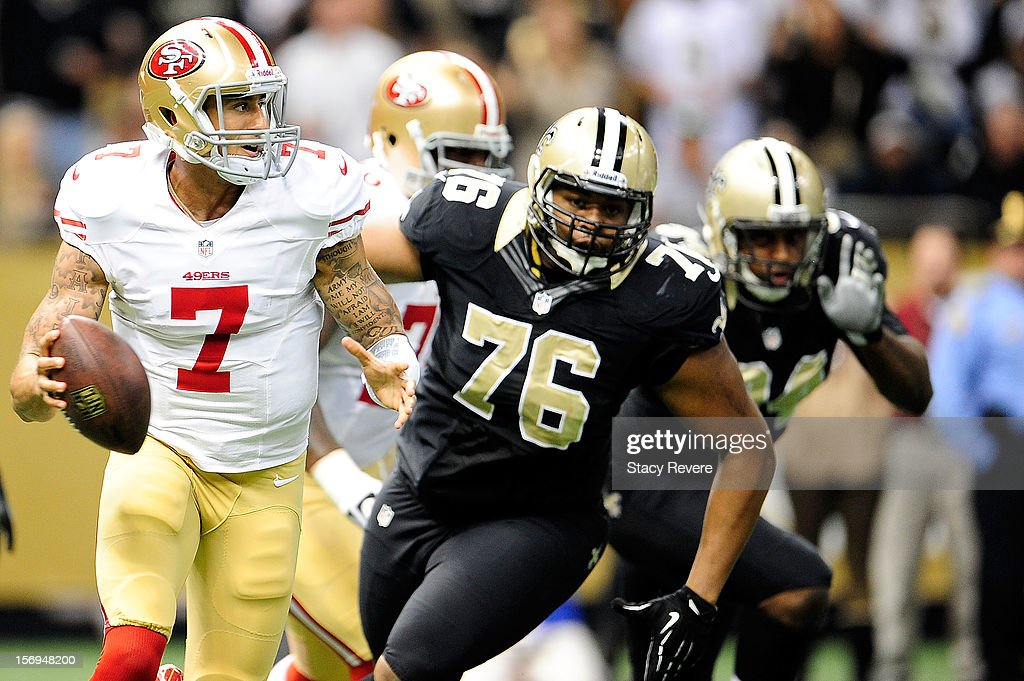 Colin Kaepernick #7 of the San Francisco 49ers is pressured by Akiem Hicks #76 of the New Orleans Saints during a game at the Mercedes-Benz Superdome on November 25, 2012 in New Orleans, Louisiana.