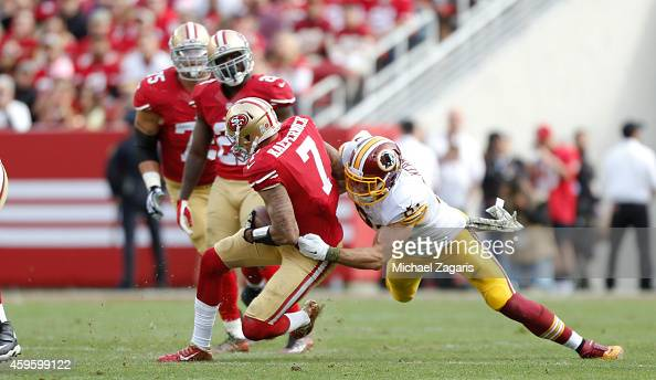 Colin Kaepernick of the San Francisco 49ers is tackles by Ryan Kerrigan of the Washington Redskins during the game at Levi Stadium on November 23...
