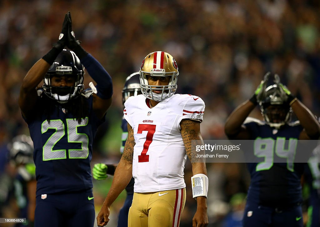 Colin Kaepernick of the San Francisco 49ers looks on as Richard Sherman and D'Anthony Smith of the Seattle Seahawks celebrate a saftey during their...