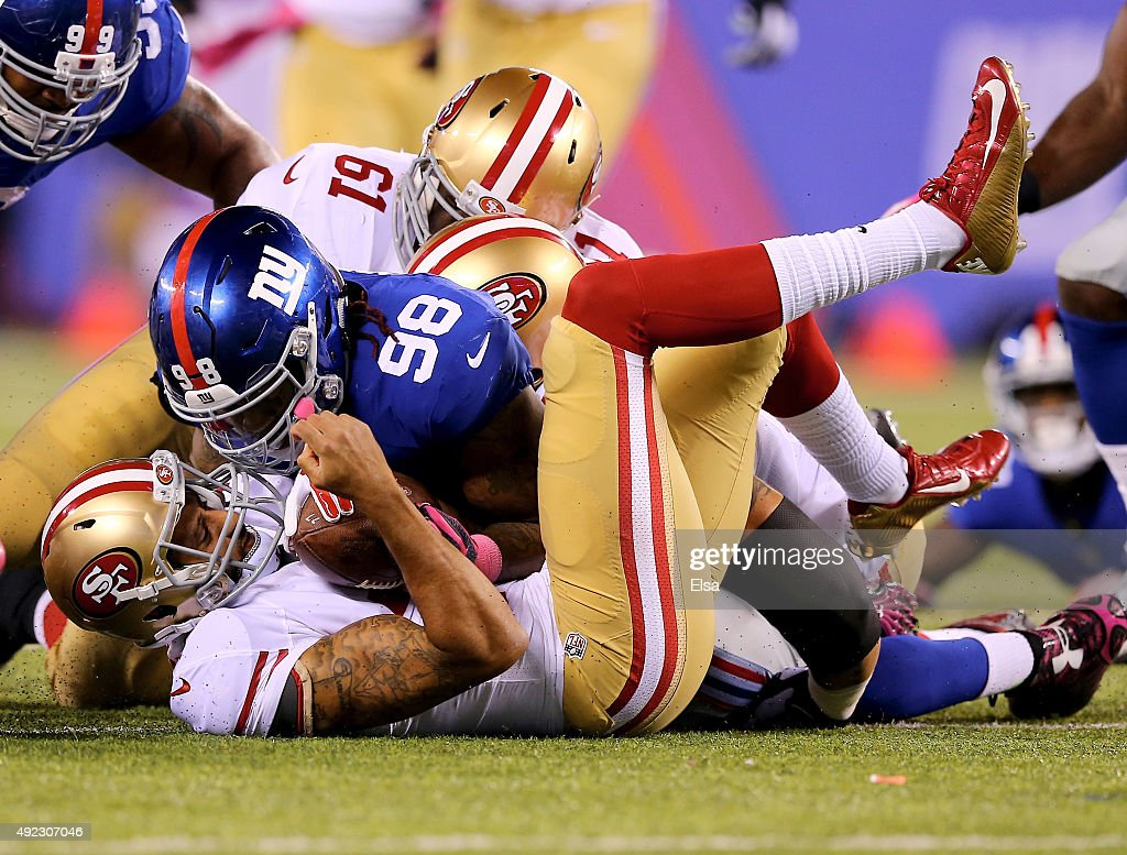 <a gi-track='captionPersonalityLinkClicked' href=/galleries/search?phrase=Colin+Kaepernick&family=editorial&specificpeople=5525694 ng-click='$event.stopPropagation()'>Colin Kaepernick</a> #7 of the San Francisco 49ers recovers his fumble as <a gi-track='captionPersonalityLinkClicked' href=/galleries/search?phrase=Damontre+Moore&family=editorial&specificpeople=8318058 ng-click='$event.stopPropagation()'>Damontre Moore</a> #98 of the New York Giants defends in the second quarter at MetLife Stadium on October 11, 2015 in East Rutherford, New Jersey.