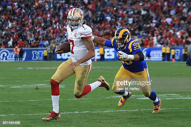 Colin Kaepernick of the San Francisco 49ers runs with the ball as he is pursued by Aaron Donald of the Los Angeles Rams during their game at Los...