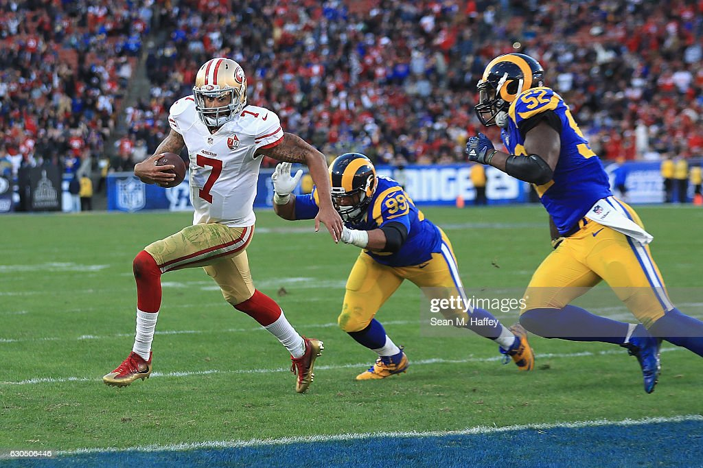 Colin Kaepernick #7 of the San Francisco 49ers rushes for a 13-yard touchdown during the fourth quarter as Aaron Donald #99 and Alec Ogletree #52 of the Los Angeles Rams attempt to tackle him at Los Angeles Memorial Coliseum on December 24, 2016 in Los Angeles, California.