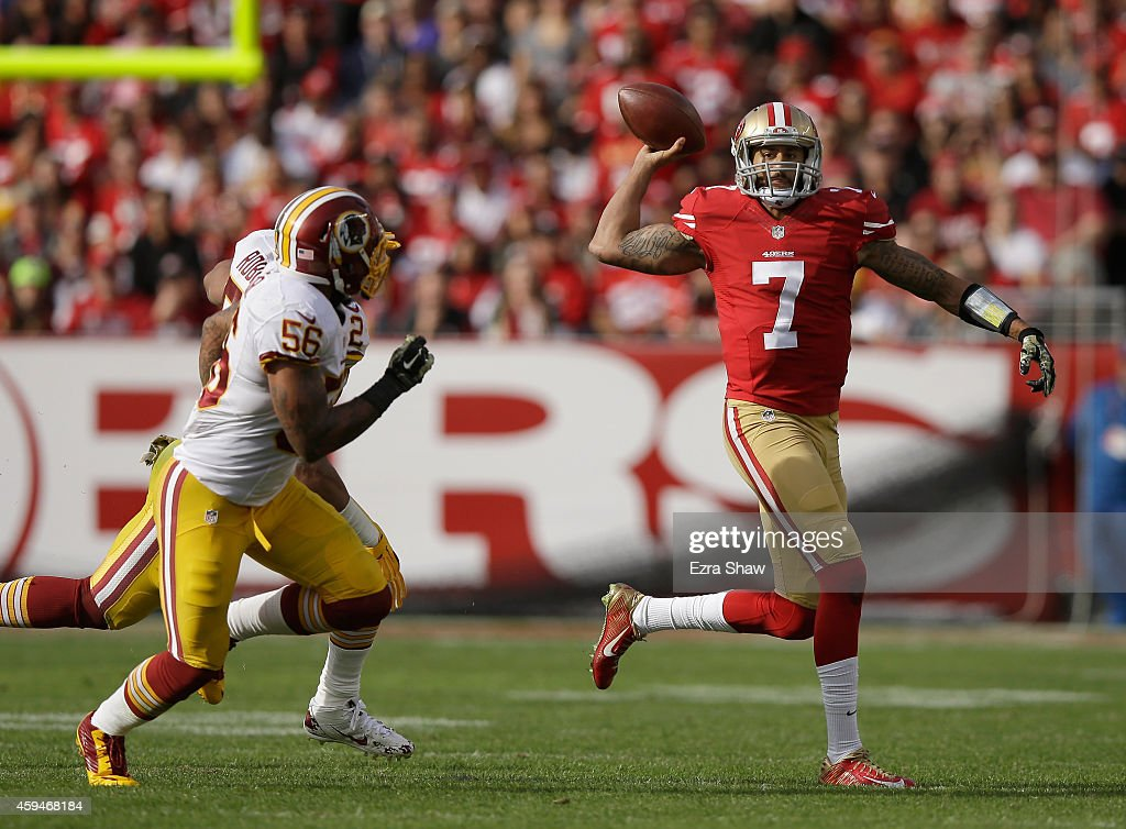 Colin Kaepernick of the San Francisco 49ers shovels a pass over Keenan Robinson of the Washington Redskins and Perry Riley of the Washington Redskins...