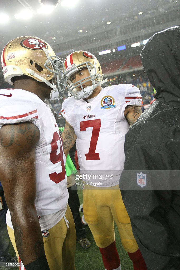 Colin Kaepernick #7 of the San Francisco 49ers talks with Aldon Smith #99 on the field prior to the game against the New England Patriots at Gillette Stadium on December 16, 2012 in Foxboro, Massachusetts. The 49ers defeated the Patriots 41-31.