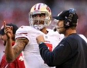 Colin Kaepernick of the San Francisco 49ers talks with head coach Jim Harbaugh on the sidelines against the Arizona Cardinals during a game at...